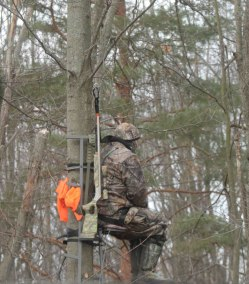 A hunter in a tree stand.  He'll use carefully delivered shots to take out a deer.